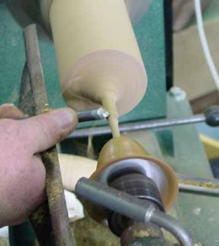 Final shaping of the thin stem is done with the edge of the bowl gouge in the skew position cutting toward the head stock
