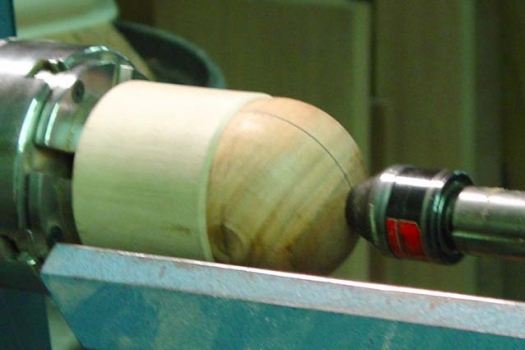 The sphere blank mounted in the jam chuck at right angles to the marked groove. Cutting just to the groove gives the perfect shpere.