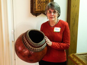 Judy A. with her giant gourd and pine needle creation