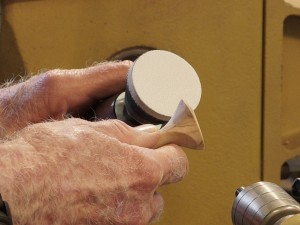 Sam uses small sanding pad to finish the handle's end